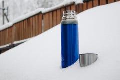 Blaue silberne Thermosflasche der Nahaufnahme mit Kaffee oder Tee im Schnee im Hinterhof Winterurlaube, heißes Getränkkonzept stockfotografie