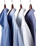 Blaue Smokinghemde auf hölzernen Aufhängungen Stockfoto