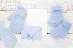Blaue Socken des kleinen Jungen, Handschuhe, leere Karte und evelop auf weißem hölzernem Hintergrund Flache Lage Lizenzfreie Stockbilder
