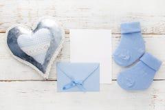 Blaue Socken des kleinen Jungen, leere Karte, evelop und Herz auf weißem hölzernem Hintergrund Flache Lage Lizenzfreie Stockfotografie