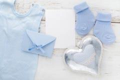 Blaue Socken des kleinen Jungen, leere Karte, evelop und Herz auf weißem hölzernem Hintergrund Flache Lage Stockfoto