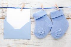 Blaue Socken des kleinen Jungen, leere Karte im evelop auf weißem hölzernem Hintergrund Flache Lage Lizenzfreies Stockbild