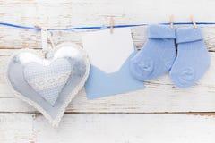 Blaue Socken des kleinen Jungen, leere Karte im evelop und Herz auf weißem hölzernem Hintergrund Flache Lage Stockfotografie