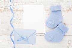 Blaue Socken des kleinen Jungen, leere Karte und evelop auf weißem hölzernem Hintergrund Flache Lage Stockfotografie