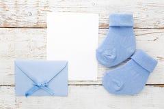 Blaue Socken des kleinen Jungen, leere Karte und evelop auf weißem hölzernem Hintergrund Flache Lage Lizenzfreies Stockbild