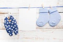 Blaue Socken des kleinen Jungen, leere Karte und Overall auf weißem hölzernem Hintergrund Flache Lage Lizenzfreie Stockfotografie
