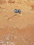 Blaue Sommerfußabnutzung auf dem mit gelbem Sand der Küste Lizenzfreie Stockbilder