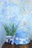 Blaue Sonnenhut- und -lavendelblumen gegen alte gebrochene Wand in Griechenland Stockfotos