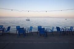 Blaue Stühle durch das Meer Stockfotografie