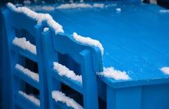 Blaue Stühle unter Schnee Stockfoto