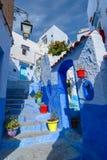 Blaue Straße mit Farbtöpfen in Chefchaouen Stockfotografie