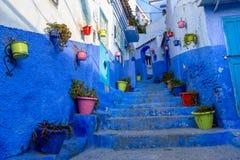 Blaue Straße mit Farbtöpfen in Chefchaouen Stockfotos