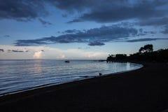 Blaue Stunde über ruhigem Ozean und schwarzem Sandstrand stockfotografie
