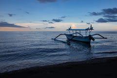 Blaue Stunde über ruhigem Ozean und schwarzem Sandstrand mit Balineseboot stockbild