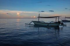 Blaue Stunde über ruhigem Ozean und schwarzem Sandstrand mit Balineseboot stockfoto