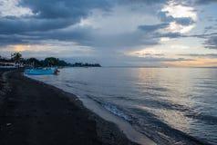 Blaue Stunde über ruhigem Ozean und schwarzem Sandstrand mit Balineseboot stockfotos