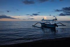 Blaue Stunde über ruhigem Ozean und schwarzem Sandstrand mit Balineseboot lizenzfreies stockbild