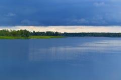 Blaue Sturmwolken über dem Fluss Stockbild