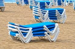 Blaue Sun-Ruhesessel gestapelt auf einem Strand lizenzfreie stockfotografie
