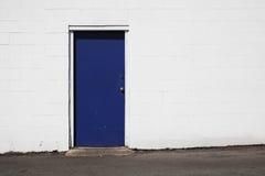 Blaue Tür auf weißem Gebäude Lizenzfreie Stockfotos