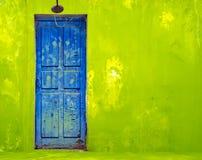 Blaue Tür in der schäbigen grünen Wand Lizenzfreies Stockbild