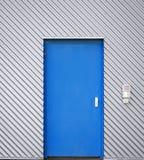 Blaue Tür in einer Fassade des Wellblechs stockfotografie