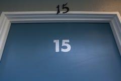 Blaue Tür mit der Nr. fünfzehn zweimal beschriftet auf ihr Stockbilder