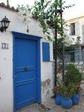 Blaue Tür mit weißem Bouganvilla Stockbild