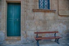 Blaue Tür und ein Fenster mit einer hölzernen Straße setzen auf die Bank Stockfoto