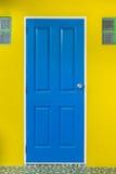 blaue Tür wird mit gelber Wand zugeschlossen Stockfotos