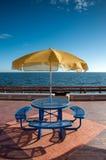 Blaue Tabelle und gelber Regenschirm Lizenzfreie Stockfotos