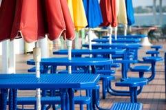 Blaue Tabellen mit bunten Regenschirmen Stockfoto