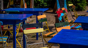 Blaue Tabellen mit colorfull Stühlen Stockfotos