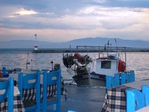 blaue Tabellen und Sonnenuntergang auf dem Strand in Griechenland Lizenzfreie Stockbilder