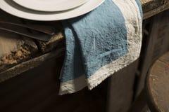 Blaue Tafelserviette, die vom Rand des Holztischs baumelt Lizenzfreie Stockfotos
