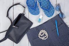 Blaue Tasche, Sonnenbrille, Flipflops, Nagellack und wenig Flugzeug auf weißem hölzernem Hintergrund lizenzfreie stockfotografie