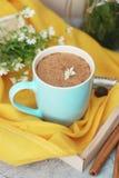 Blaue Tasse Kaffee-Milch Latte-Getränk-Zimtstange-hölzerne Hintergrund-Gelb-Servietten-rustikale Kamillen-Blume Buquet-Ebenen-Lag lizenzfreies stockbild