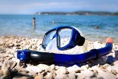 Blaue Tauchensschutzbrillen auf Seestrand Stockfoto