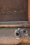 Blaue Tennisschuhe auf Fußmatte Stockfoto