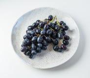 Blaue Trauben auf der weißen Tabelle auf der Platte Lizenzfreie Stockfotos
