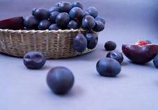 Blaue Trauben in einem silbernen Korb auf einem grauen Hintergrund lizenzfreie stockfotos