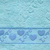 Blaue Tuch-Beschaffenheit mit Liebes-Text und Herzen stockfoto