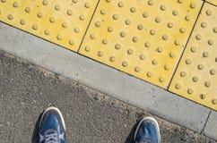 Blaue Turnschuhe auf gelben Tastpflastersteinen Lizenzfreie Stockfotos