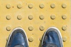 Blaue Turnschuhe auf gelben Tastpflastersteinen Lizenzfreies Stockfoto