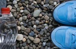 Blaue Turnschuhe auf Kieseln lizenzfreie stockfotos