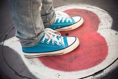 Blaue Turnschuhe, Jugendlichfüße, die auf Abwasserkanaleinsteigeloch stehen Stockbild
