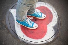 Blaue Turnschuhe, Jugendlichfüße stehen auf städtischer Straße Stockfotos