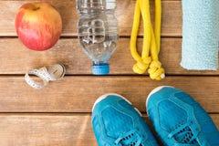 Blaue Turnschuhe und Sportzubehör auf hölzernem Hintergrund heal stockfotos