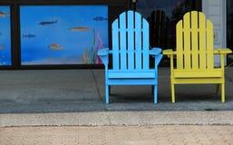 Blaue und gelbe Adirondack-Stühle, damit Besucher an sitzen Lizenzfreie Stockfotos