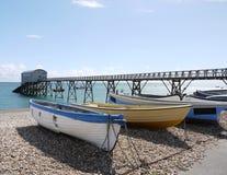 Blaue und gelbe Boote auf Selsey Pebble Beach Stockbilder